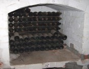 The photograph shows the wine cellar with old wine bottles.